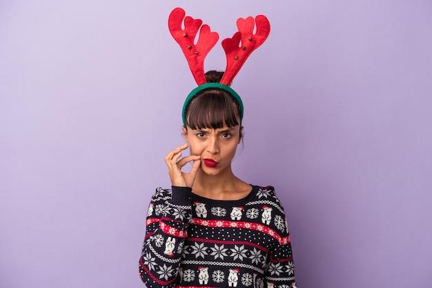Молодая женщина смешанной расы в шляпе оленя празднует рождество, изолированную на фиолетовом фоне с пальцами на губах, сохраняя в секрете.