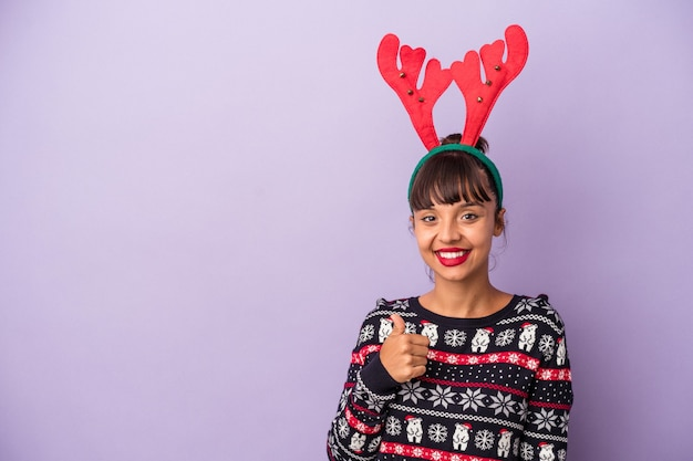Young mixed race woman with reindeer hat celebrating christmas isolated on purple background  smiling and raising thumb up