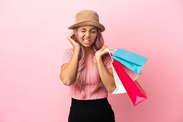 Молодая женщина смешанной расы с хозяйственной сумкой, изолированной на розовом фоне, разочарована и закрывает уши