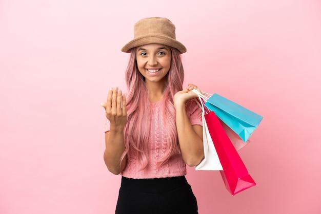 Молодая женщина смешанной расы с хозяйственной сумкой, изолированной на розовом фоне, приглашая прийти с рукой. счастлив что ты пришел