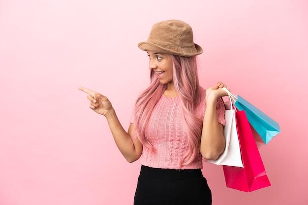 Молодая женщина смешанной расы с хозяйственной сумкой, изолированной на розовом фоне, указывая пальцем в сторону и представляя продукт