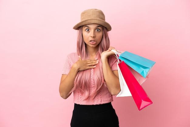 ピンクの背景に分離されたショッピングバッグを持つ若い混血の女性は、右を見ながら驚いてショックを受けました