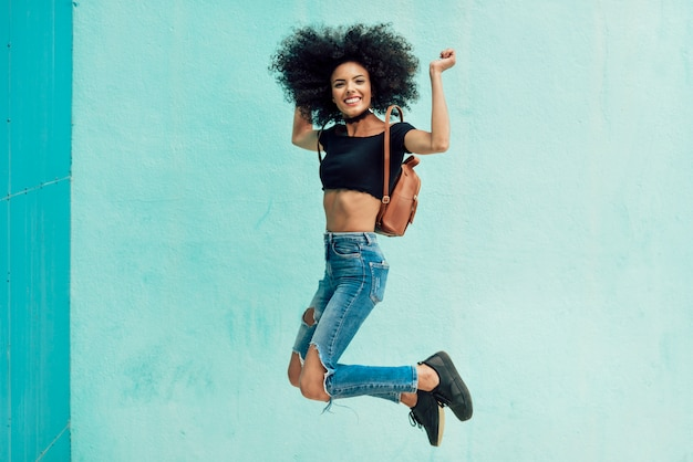 Young mixed woman with afro hair jumping outdoors.
