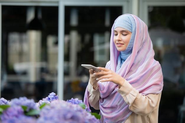 屋外で時間を過ごしながらスマートフォンで花の写真を撮るヒジャーブの若いモバイル女性