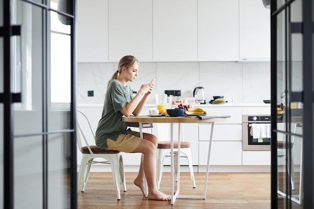 Молодая мобильная женщина с смартфон текстовых сообщений на стол