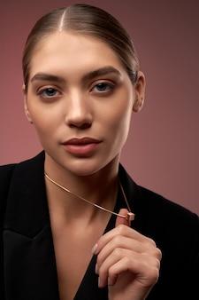 金色のネックレスを示す若いモデル
