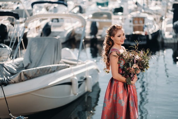 Young model girl in a beautiful dress with a bouquet of flowers on the beach in france. girl with flowers in spring provence on the french riviera.