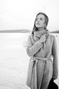 Young model girl in gray coat and black hat  posed against freeze lake. black and white photo.