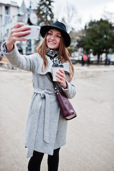 Young model girl in a gray coat and black hat with leather handbag on shoulders stay with plastic cup of coffee