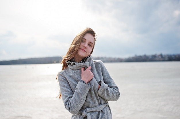 Young model girl in gray coat with red hair against freeze lake.