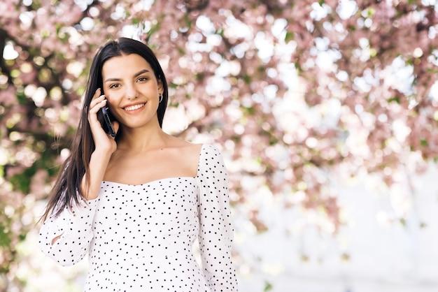 공원에서 산책하는 전화 통화하는 젊은 모델 소녀