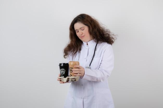 Giovane modella ragazza in uniforme bianca che tiene un cartone con tazze di caffè.