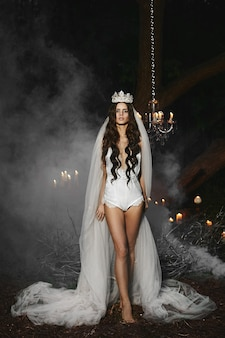 Young model girl with a gentle makeup in a white lingerie with a crown and veil on her head posing outdoors in foggy forest