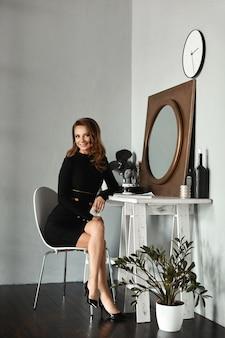 빈티지 인테리어의 화장대에 앉아 짧은 검은 드레스에 슬림 바디와 젊은 모델 소녀