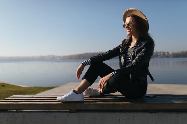 La giovane donna della ragazza di modello che posa nel giorno di autunno al lungomare del lago si è vestita in abiti casual