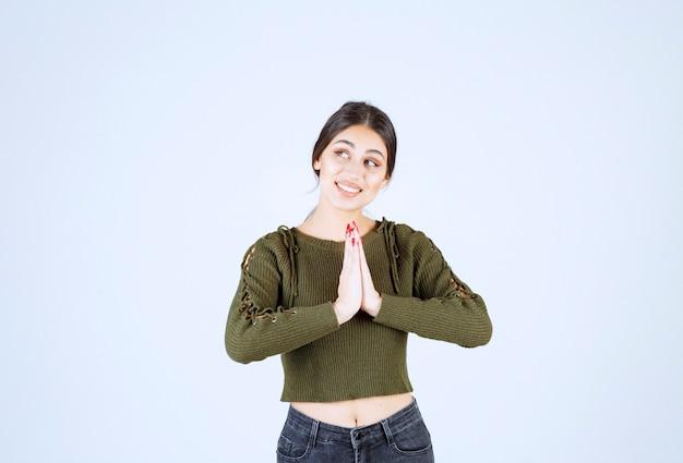 Un giovane modello in camicetta verde che prega sopra il muro bianco