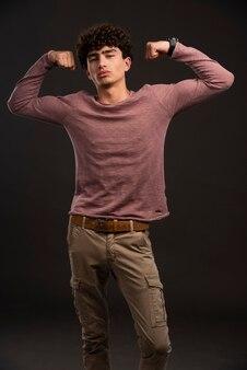 彼の筋肉を示すカジュアルな秋冬の衣装の若いモデル。