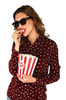 Young model in glasses eating popcorn and posing