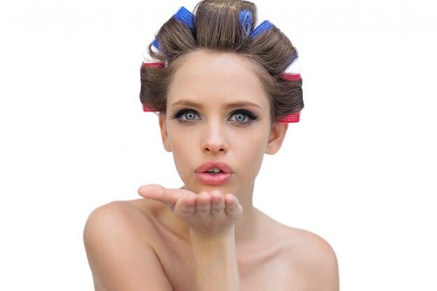 キスを吹くヘアローラの若いモデル