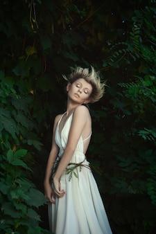 Молодая модель позирует феей в лесу