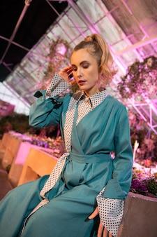 若いモデル。温室に座りながら髪に触れる素敵な美女