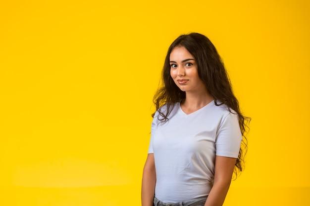 黄色の壁にポーズをとって笑っている若いモデル。