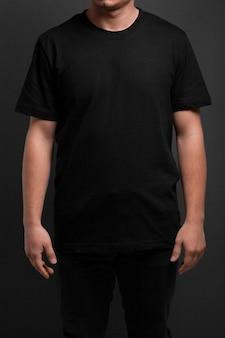 灰色の上の黒いtシャツでポーズをとる若いモデル