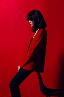Молодая модель позирует в модном красном костюме и черные брюки, изолированных на красном фоне.