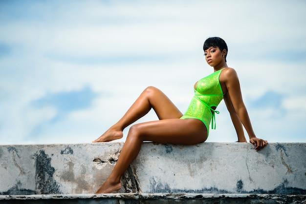 緑の水着でポーズをとる若いモデル