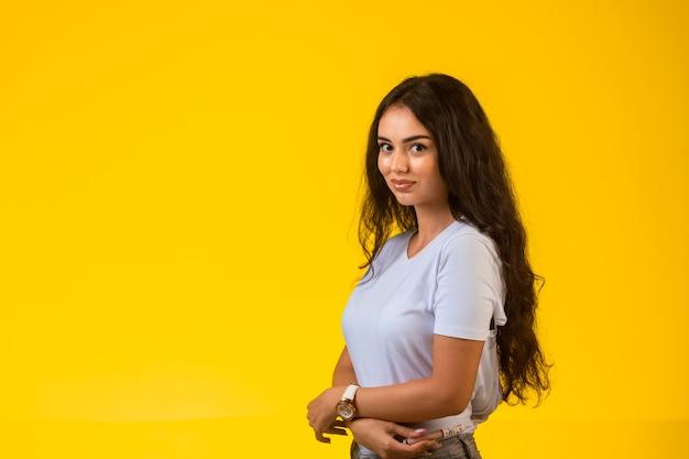 Giovane modello che propone alla parete gialla.