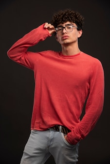 Young model in red shirt holding eyeglasses.