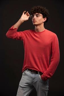 Giovane modello in camicia rossa che indossa occhiali da vista.