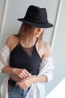 若いモデルは、カジュアルな夏服を着て頭に黒い帽子をかぶって頭を下げた状態で、スタジオの明るい壁に立っています。