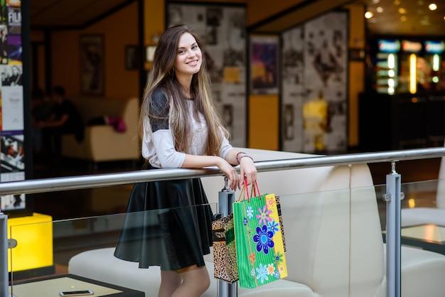 Юная модель гуляет по городу и занимается покупками в элегантном платье.