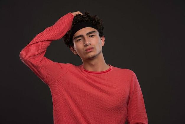 Giovane modello con i capelli ricci che toccano la sua testa.