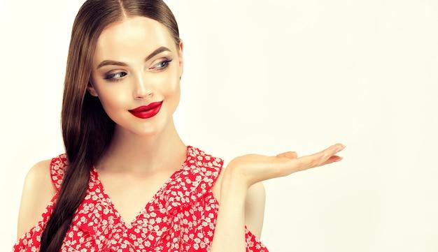 얼굴에 장난스런 표정과 매력적인 미소를 가진 젊은 모델은 복사 공간이있는 손에 제품을 보여줍니다.