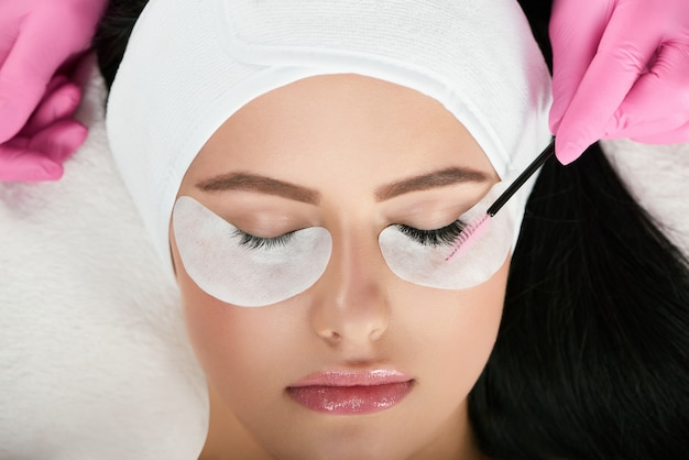 Young model with pretty face lying during lashes enlarging