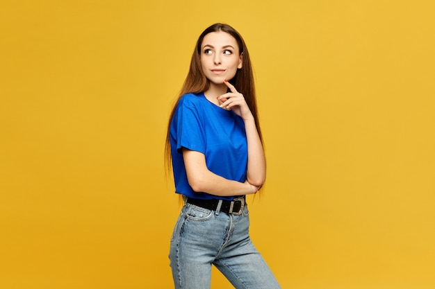 Young model with slim body in a blue oversized t-shirt and jeans looking aside and posing at the yellow wall, isolated