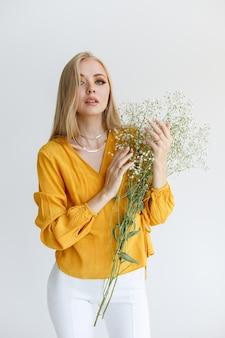 明るい背景に花と化粧と白い髪の若いモデル。秋の気分
