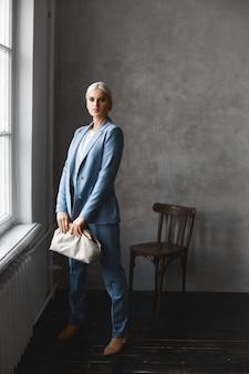 트렌디 한 파란색 정장과 세련된 지갑이있는 젊은 모델 여자가 빈티지 미니멀리스트 인테리어에 포즈