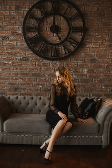 소파에 앉아 아래를 내려다 보면서 검은 드레스에 젊은 모델 여자