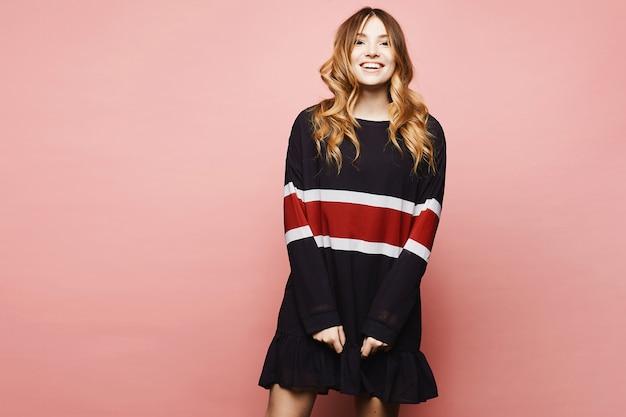 Молодая модельная женщина в негабаритном платье позирует