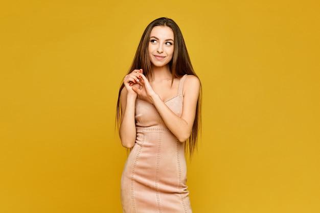 黄色の背景に短いベージュのドレスを着た若いモデルの女性。