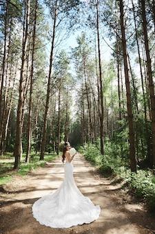 花束を保持し、森の中でポーズをとるスタイリッシュなレースのウェディングドレスの若いモデルの女性。