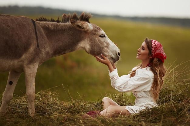 牧草地でかわいいロバとポーズをとって白い短いガウンの若いモデルの女性
