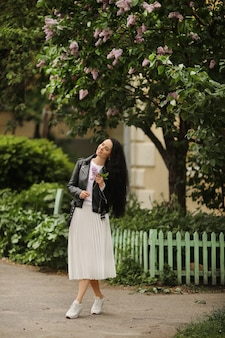 白いスカートと黒い革のジャケットを着た若いモデルの女性が、春の日に咲くライラックの木を楽しんでいる
