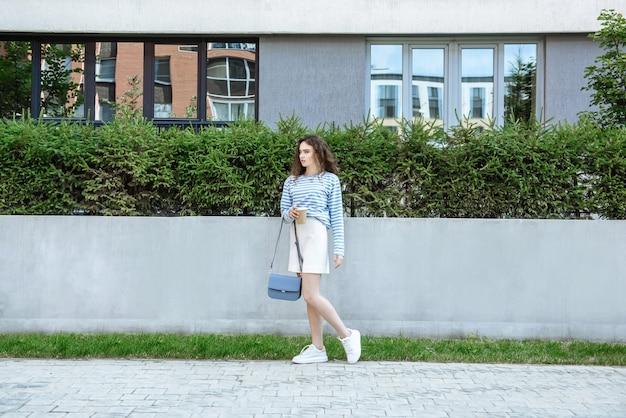 새로운 여름 옷 컬렉션에서 도시 거리의 배경에 포즈를 취하는 젊은 모델 여성