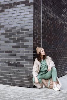 젊은 모델 여자 모자와 플라톤에 도시 현장에 앉아 포즈