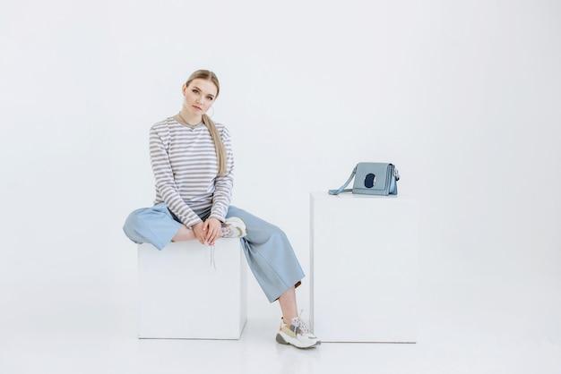 Молодая модель женщина сидит на белой сцене в студии на кубе в виде стула и смотрит вперед