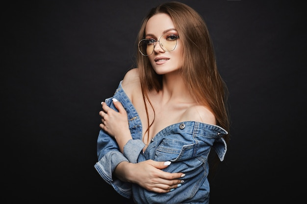 Young model woman in trendy glasses and denim jacket posing
